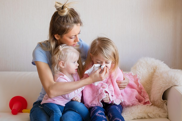 Mother of two little children helping her sick child